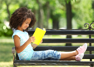 Image of a child on a parkl bench reading